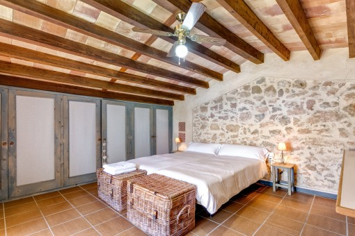 A stylish natural stone wall is decorating the bedroom