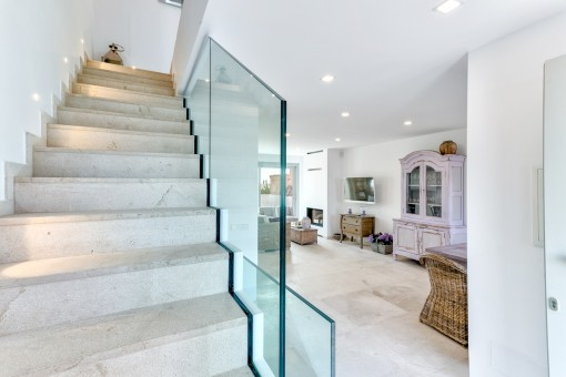 A staircase leads from the open living area to the upper floor