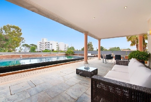 Covered lounge area next to the swimming pool