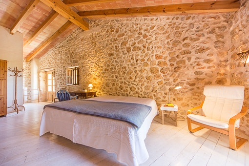 Beautiful master bedroom with natural stone wall