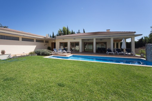 Exterior view of the villa with pool and well-tended garden