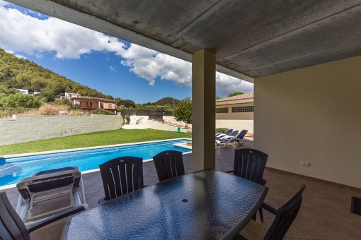 Covered terrace with dining area beside the pool