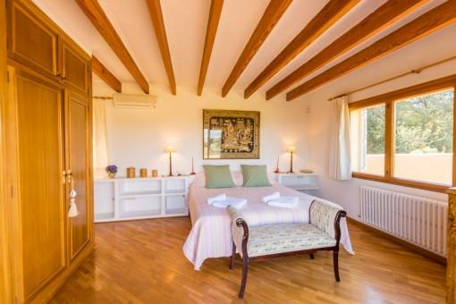 Spacious bedroom with wooden wardrobe