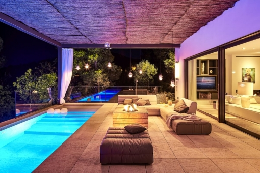 Covered terrace with pool by night