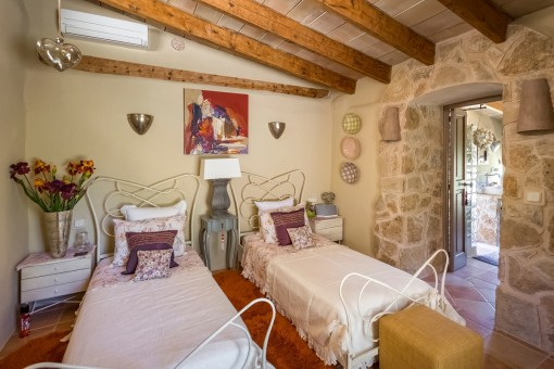 Bedroom with two single beds and natural stone wall