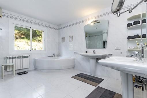 Spacious bathroom with bathtub and natural light