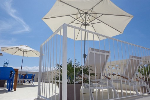 Sunny roof terrace with sunloungers