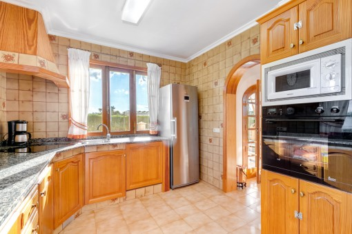 The bright kitchen provides sufficient space and fitted cupboards