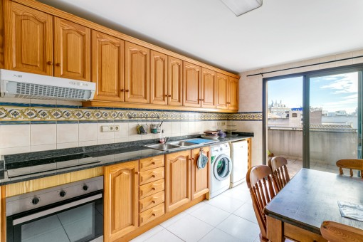 Separate and fully equipped kitchen with dining table and terrace access