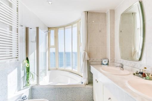 Bright bathroom with bathtub and sea views