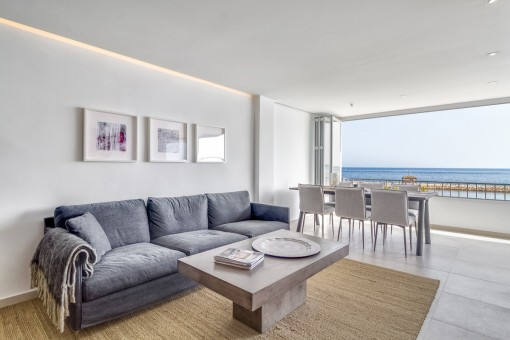 Living and dining area with open window frontage and sea views