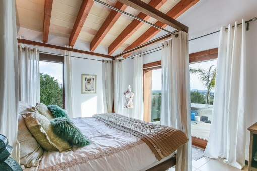 Bright bedroom with wooden ceiling beams