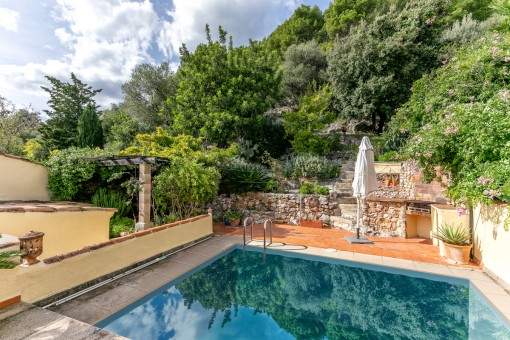 Well maintained pool area with stone wall