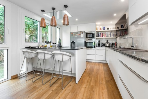 Modern, fully-equipped kitchen with bar table