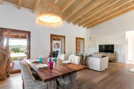 Living and dining area with wooden ceiling beams