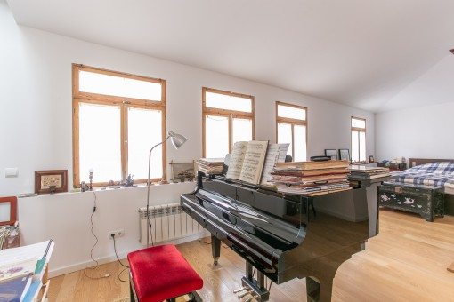 A large piano that separates the living area and bedroom